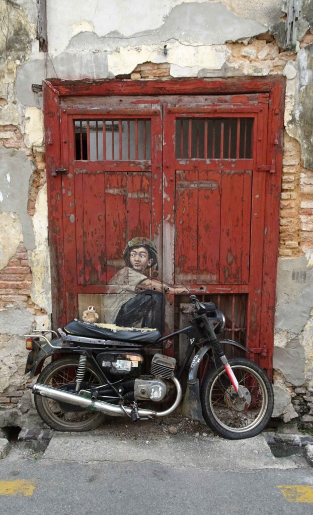 Cepat on a motorcycle attached to a street mural